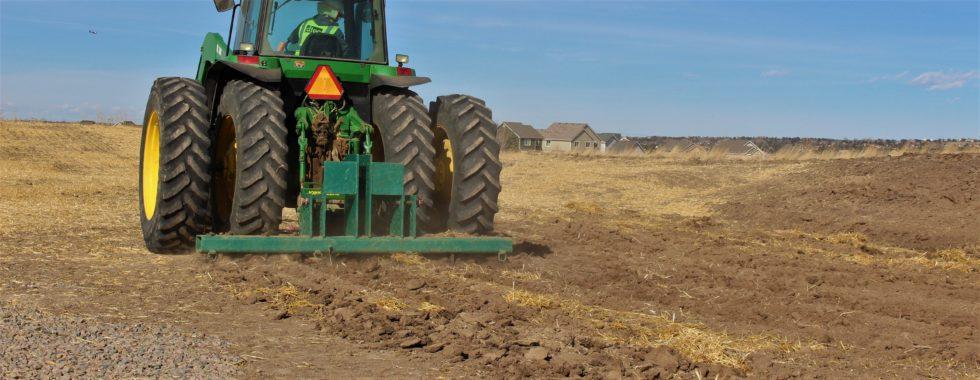Tractor prepares soil for native grass seeding